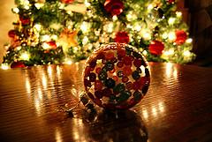 Weihnachtskugel aus Knöpfen vor Weihnachtsbaum